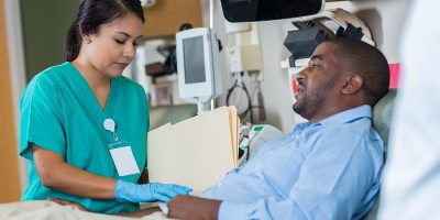 Young female Hispanic phlebotomist or nurse talks with mid adult African American male patient about his medical history. The nurse is holding a file. She is wearing scrubs and protective gloves.